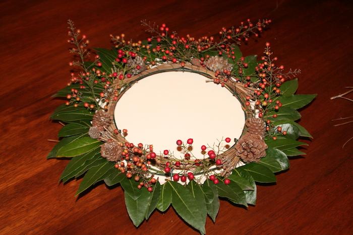 ein adventskranz mit grünen blättern und roten früchten - einen adventskranz selber binden mit braunen zapfen