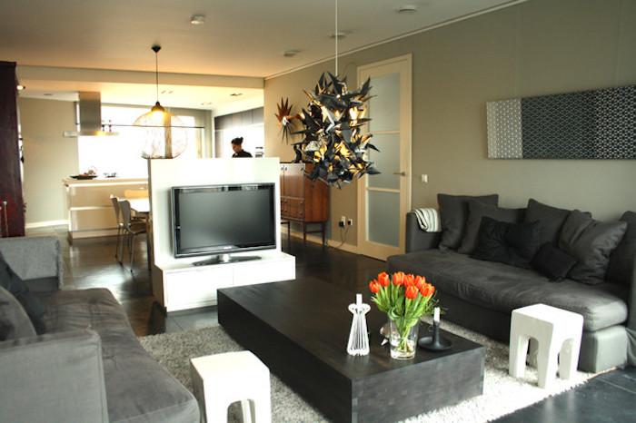 tv wand kreatives design in der mitte des zimmers wohndesign tisch zwei sofas und frische tulpen auf dem tisch küche auf der anderen seite