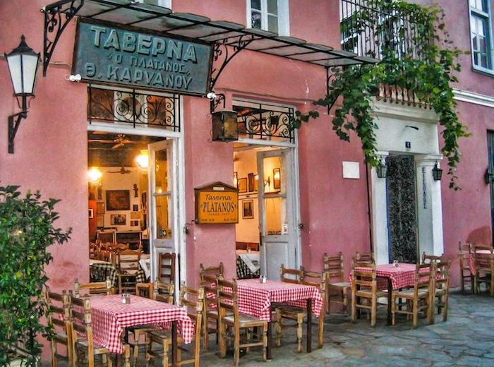 athen sehenswürdigkeiten taverna tawerna in athen gebäude in rosarot gemalen grüne pflanzen auf dem balkon über dem restaurant kleine tische mit kariierten tischdecken mediterranes essen probieren essen und genießen