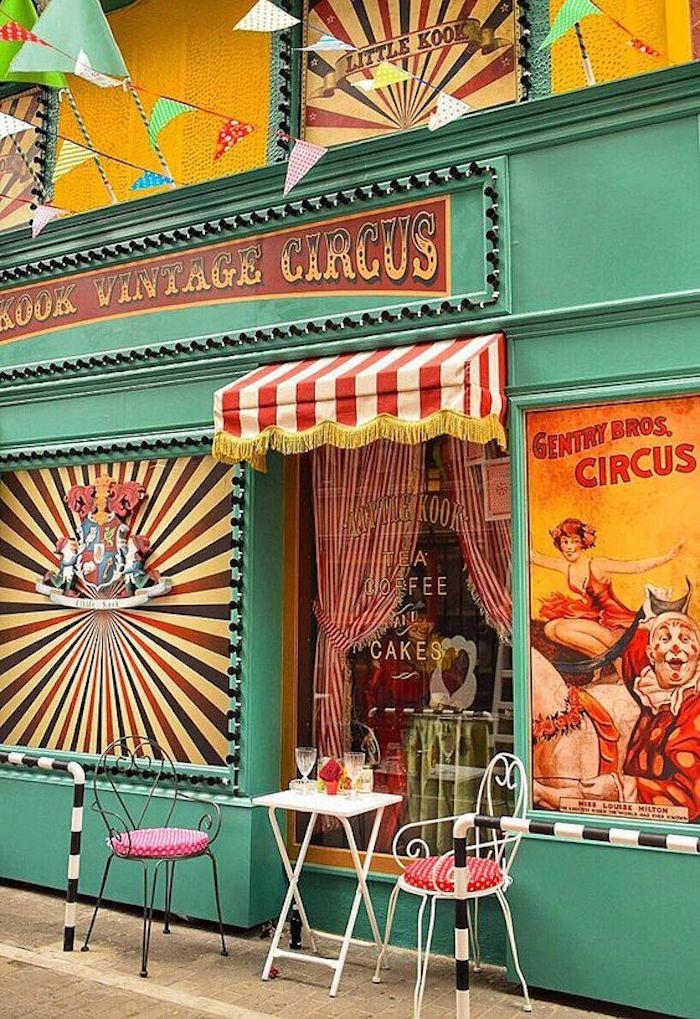 athen sehenswürdigkeiten ein faszinierendes geschäft mintgrün fassade zirkus shop mintgrüne farbe gemälde zirkusspieler clown lutscher motive deko bunte farben rosarote stühle sitzkissen