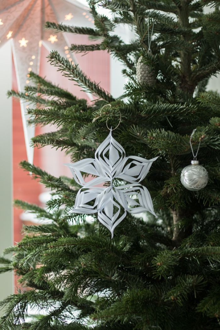 Tolle Bastelidee für Weihnachtsschmuck, Schneeflocke aus Papier selbst gemacht, silberne Dekokugel und Zapfen