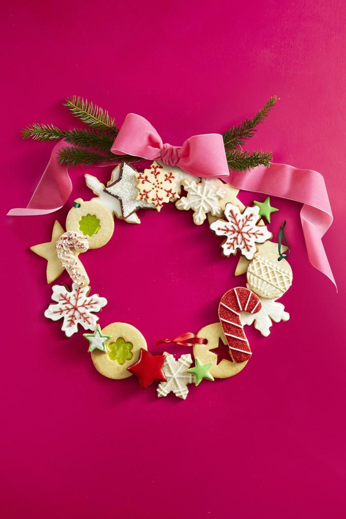Weihnachtskranz aus Keksen, mit rosafarbenem Band und Tannenzweigen verziert, tolle Idee für Weihnachtsdekoration