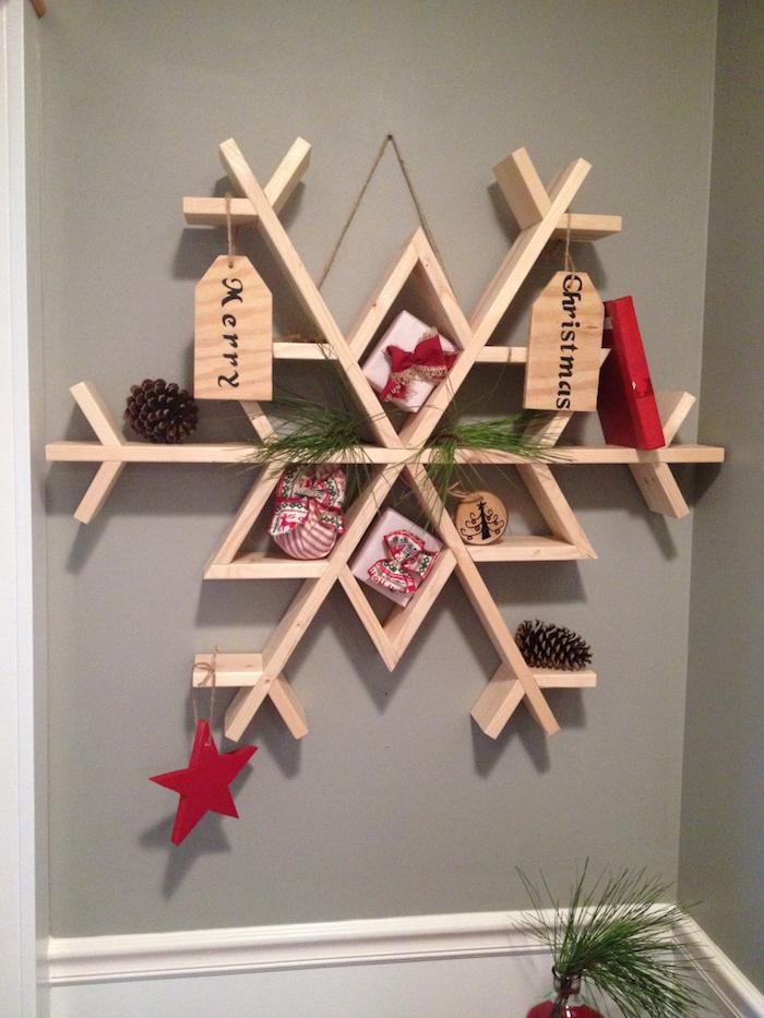 Schneeflocken Bilder - eine Schneeflocke aus Bretten mit Geschenken als Verzierung
