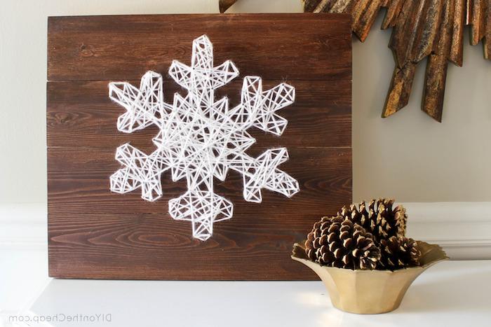 eine Schneeflocke aus Garn und Nägel auf ein Brett - Schneeflocken basteln