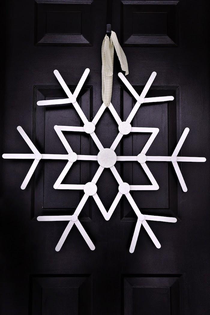 weiße Schneeflocke an einer dunklen Tür mit einem weißen Band gebunden - Schneeflocken basteln