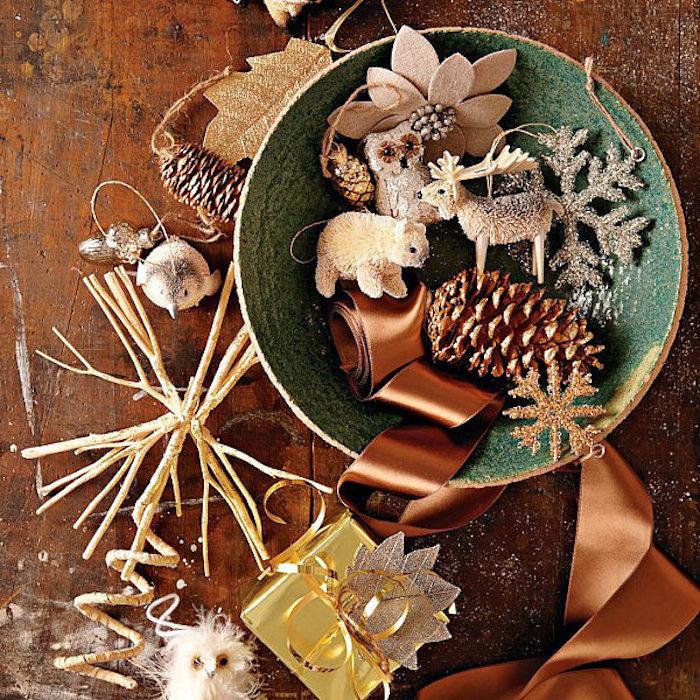 Weihnachtstischdeko schüssel voll mit kleinen dekoelementen zu weihnachen zapfen kleine figuren weihnachtsbaum schmuck schleife braun