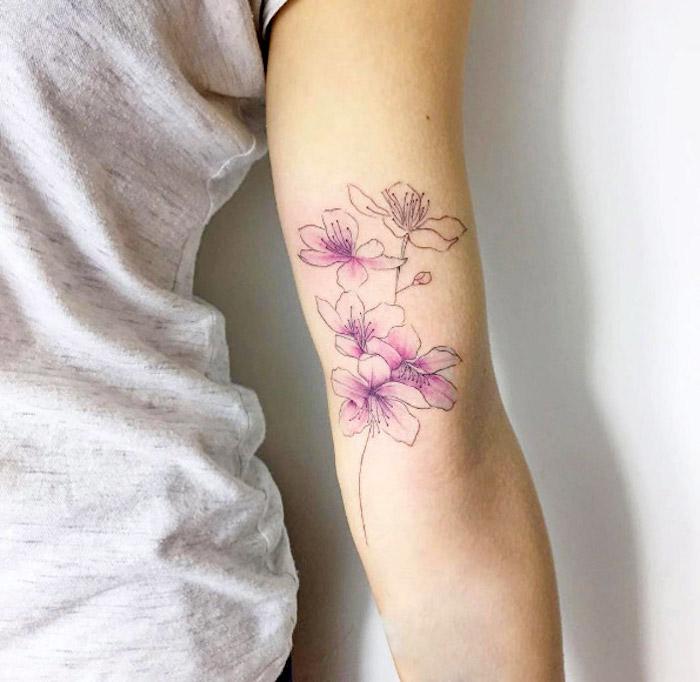 tattoos mit bedeutung, farbige tätowierung mit kirschblüten-motiv, blumen tattoos