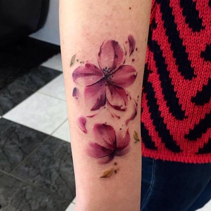 blumenranke tattoo am unterarm, rosa blüten mit wegfliegenden blüttenblättern