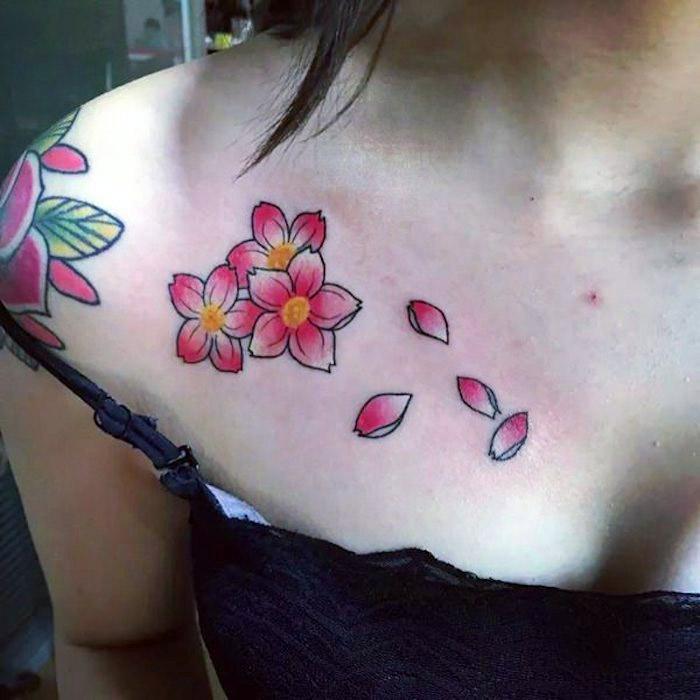 frau mit blumenranke tattoo am schulter, rosa kirschblüten mit wegfliegenden blütenblättern