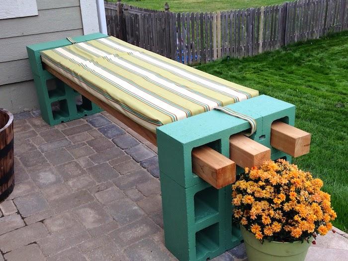 eine gartenbank aus holz und großen grünen pflanzsteinen - blumentopf mit orangen blumen - eine gartenbank selber bauen