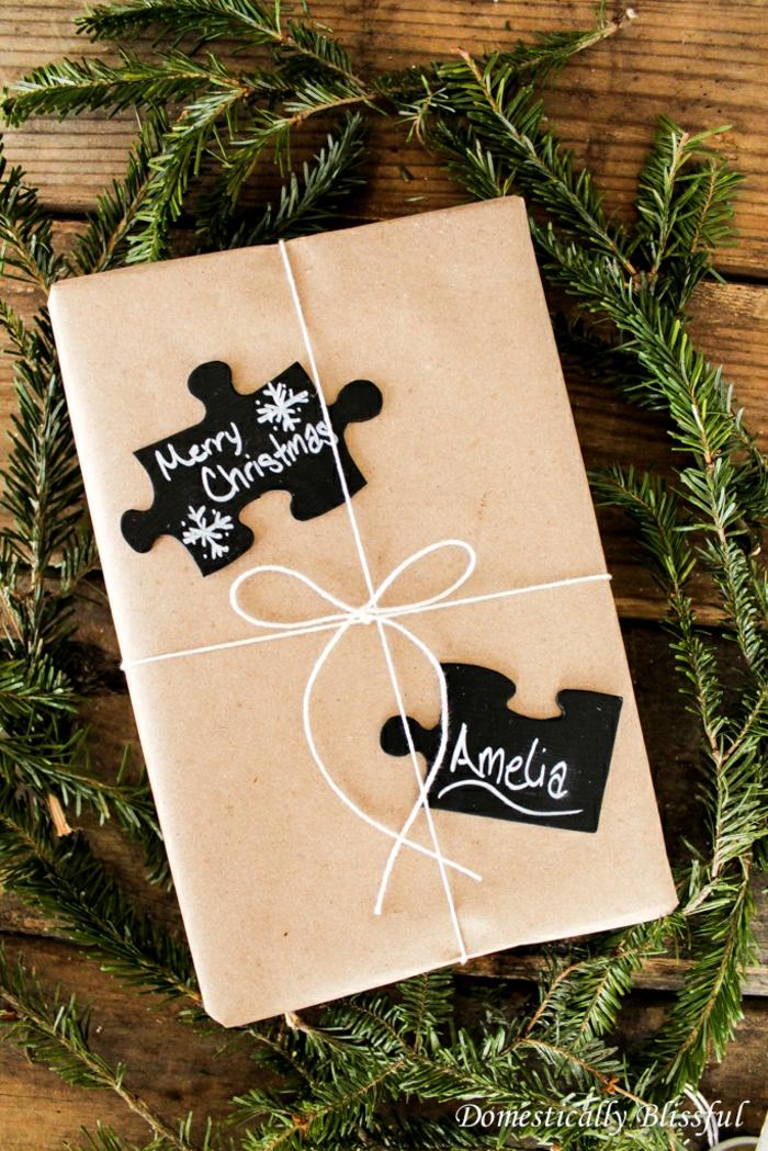 Geschenkverpackung mit Puzzlestücken verziert, kreative Geschenkideen zu Weihnachten, frische Tannenzweige