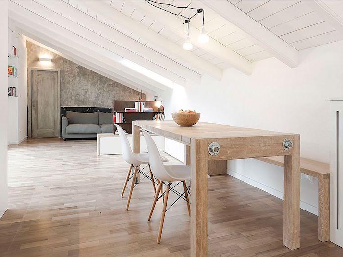 mansardenwohnung in hellen nuancen holztisch holzboden parkett sofa in grau in der wohnung obstschale bücher