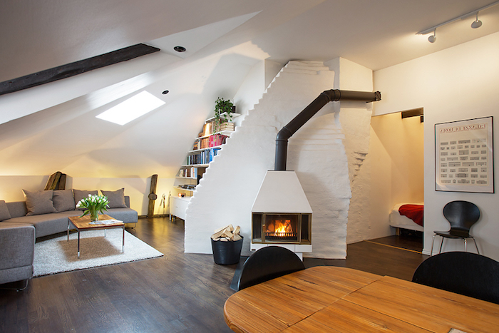 dachgeschosswohnung inspirierende ideen kamin sofa tisch esstisch stühle bücherregale wandbild schwarz weiße einrichtung frische blumen auf dem tisch