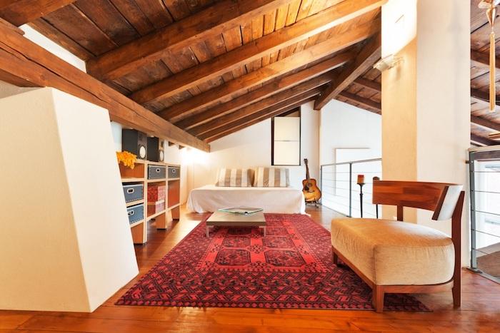 dachgeschosswohnung rote einrichtung holzdach dachschräge sofa schubladen rot schwarzer teppich bett bettdesign kissen dekorationen