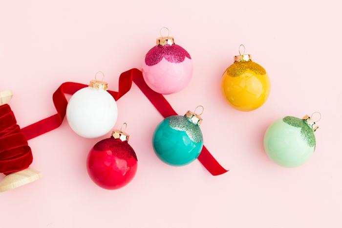 Bunte Weihnachtskugeln selbst verzieren, mit Glitzer besprühen, roter Dekoband, Bastelidee für Weihnachten