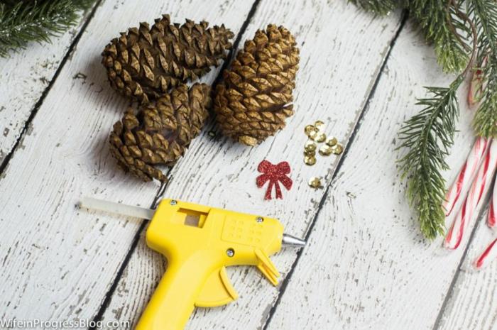 Zapfen selber verzieren, Pailletten mithilfe einer Heißklebepistole befestigen, DIY Ideen für Weihnachtsschmuck