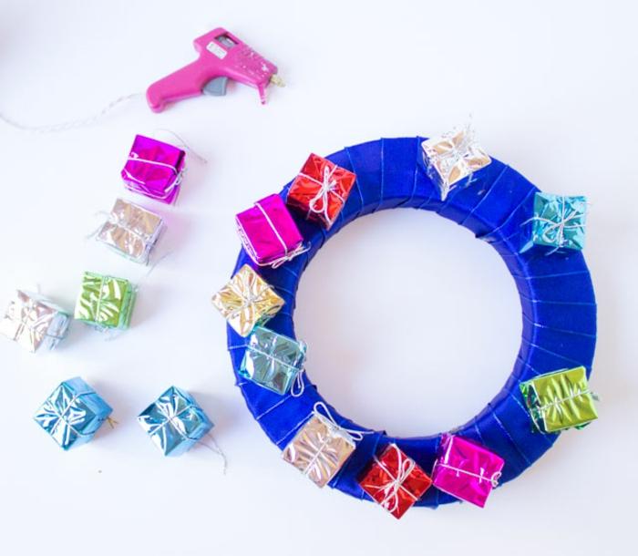 Weihnachtskranz selber machen, kleine Geschenke mithilfe einer Heißklebepistole befestigen