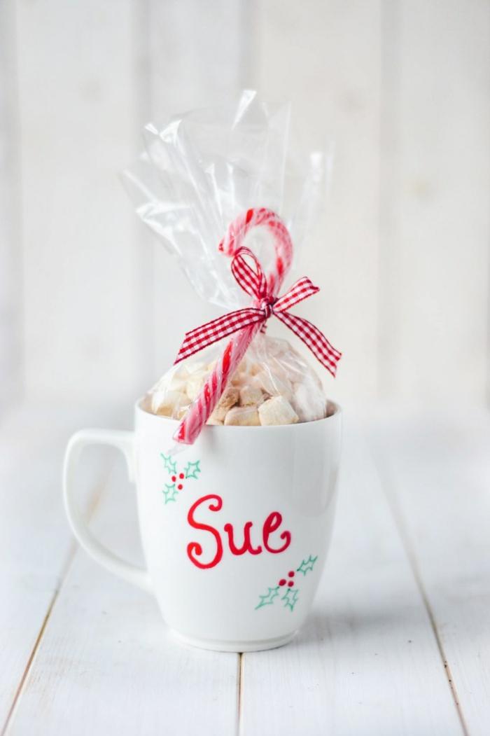 Weiße Tasse mit Permanentmarkern beschriftet, mit Marshmallows befüllt, Zuckerstange mit Band befestigt