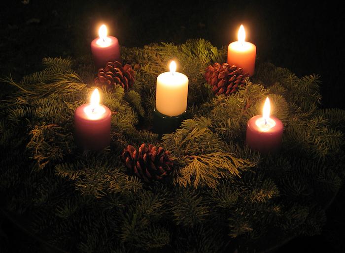 einen adventskranz selbst binden - ein adventskranz mit kleinen braunen zapfen und vier kleinen pinken kerzen und einer kleinen weißen kerze