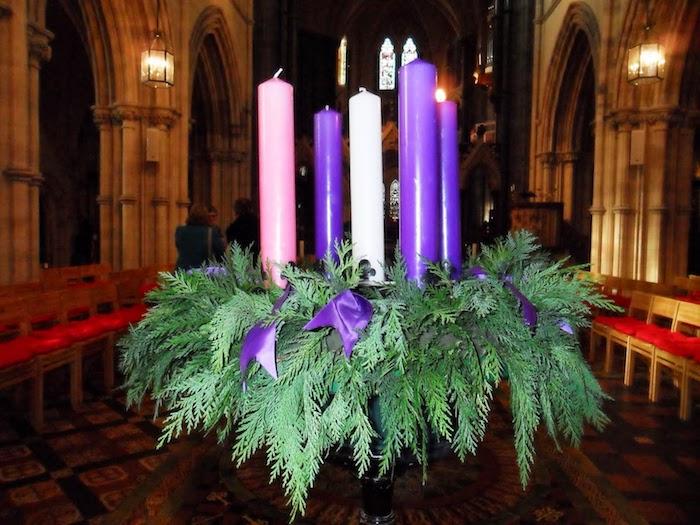 ein adventskranz mit ästen mit grünen blättern und mit drei lila kerzen, einer weißen kerze und einer pinken kerze