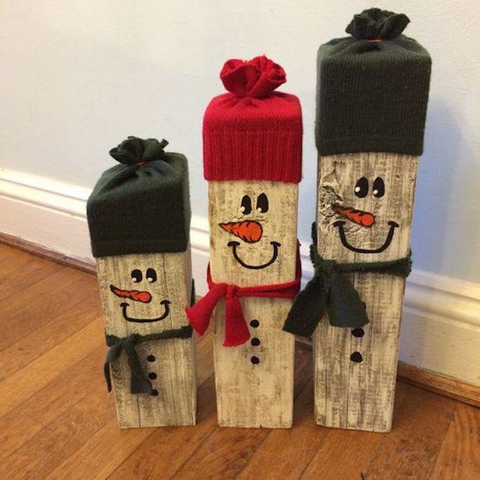 schneemann selber basteln aus holz - drei schneemänner mit orangen nasen, kleinen schwarzen augen und schwarzen und roten hüten