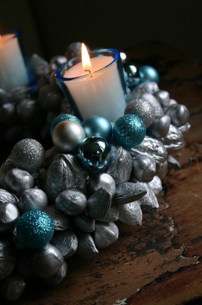 adventskranz selber basteln - ein kranz mit grauen und pinken bällen und einer kleinen weißen kerze mit feuer