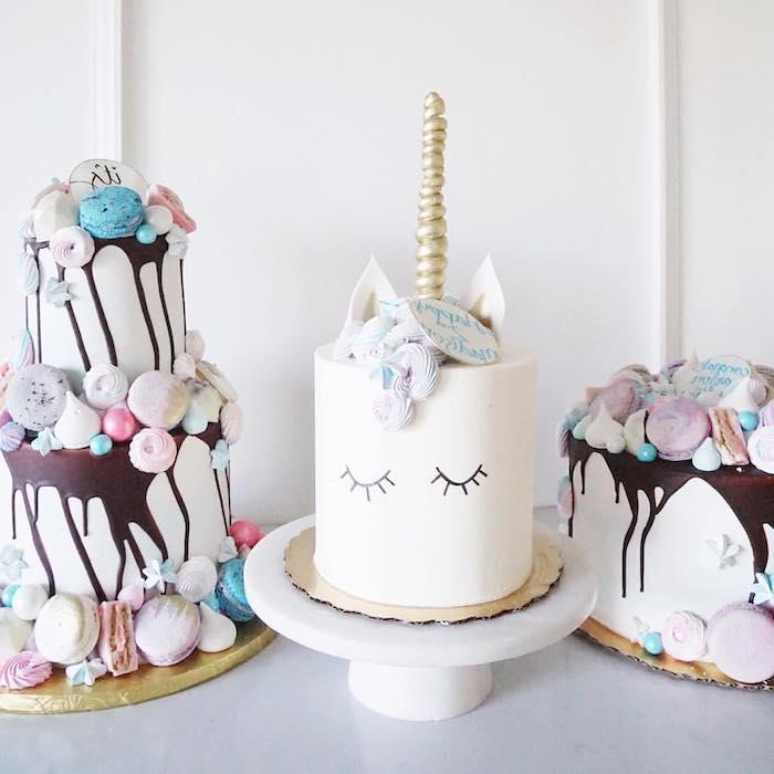 idee für eine weiße einhorn torte mit einem weißen einhorn mit einem langen gelben einhorn und mit schwarzen augen und eine zweistöckige weiße torte mit schokolade
