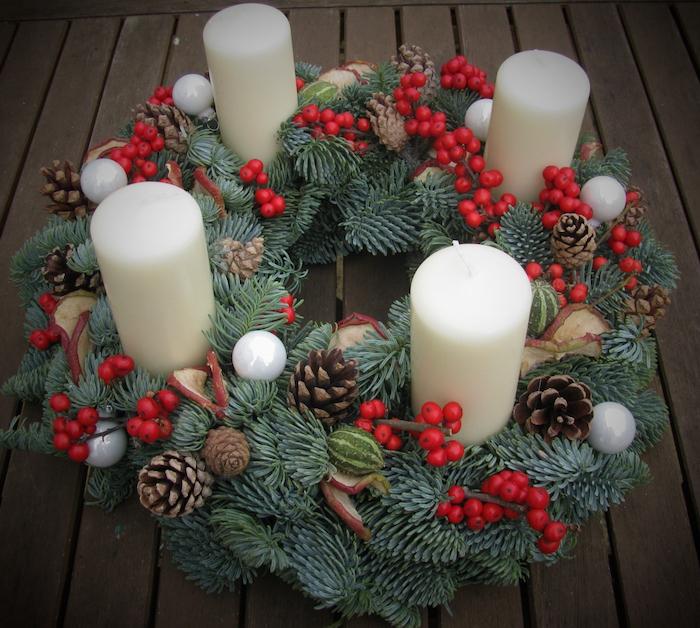 vier weiße kleine kerzen - ein adventskranz mit kerzen,, kleinen weißen bällen und braunen zapfen