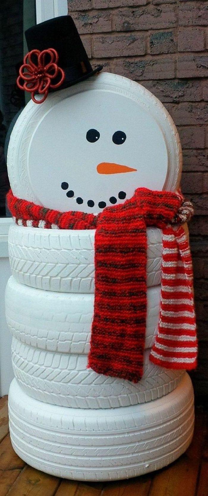 großer schneemann mit einem roten schal, einem schwarzen hut und einer orangen nase - schneemann aus weißen reifen