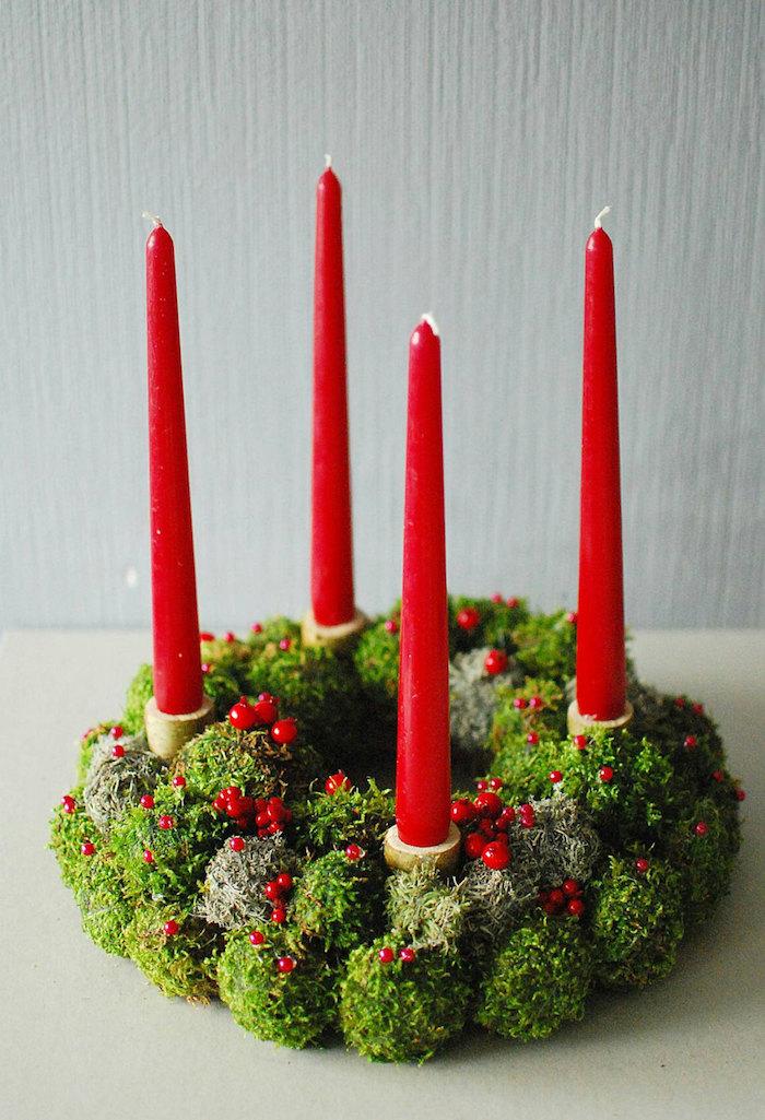 ein großer adventskranz mit kleinen roten früchten und vier langen großen roten kerzen und grünen pflanzen - einen adventskranz selber binden