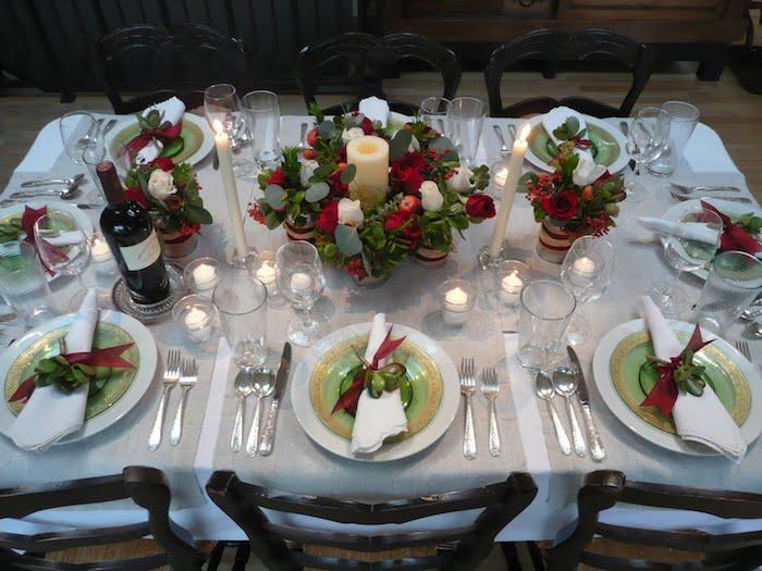 zum thema weihnachtsdekoration - ein tisch, teller, löffel, messer und ein großer adventskranz mit kerzen und grünen blättern