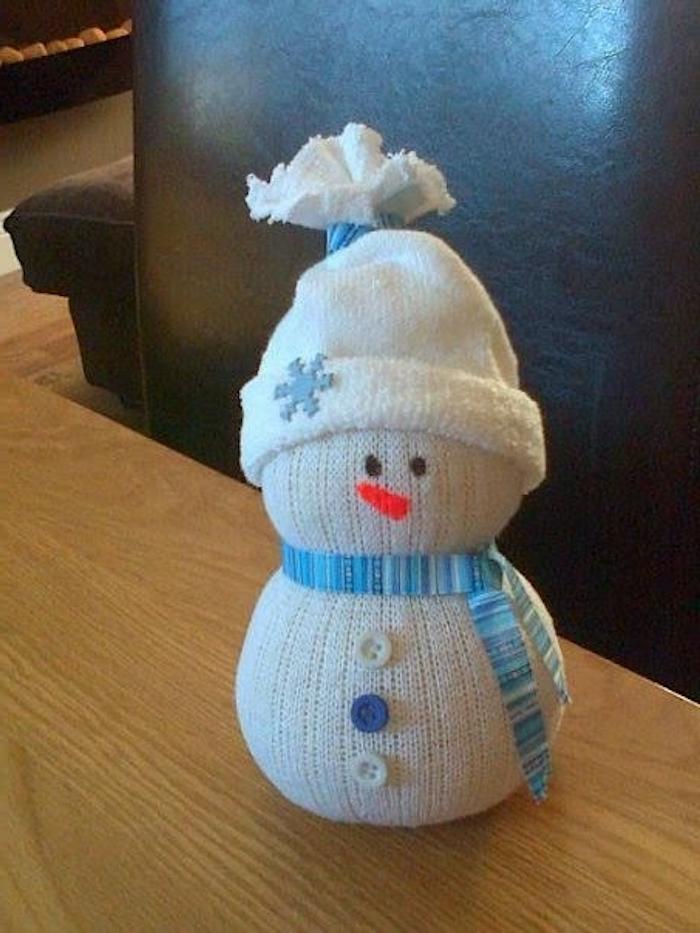 kleiner weißer schneemann mit einem blauen schal und drei lila und weißen knöpfen - schneemann aus socken basteln