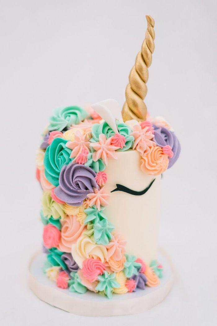weiße einhorn torte mit einem einhorn mit einer bunten langen mähne aus lila grünen und pinken rosen aus sahne und einem goldenen horn