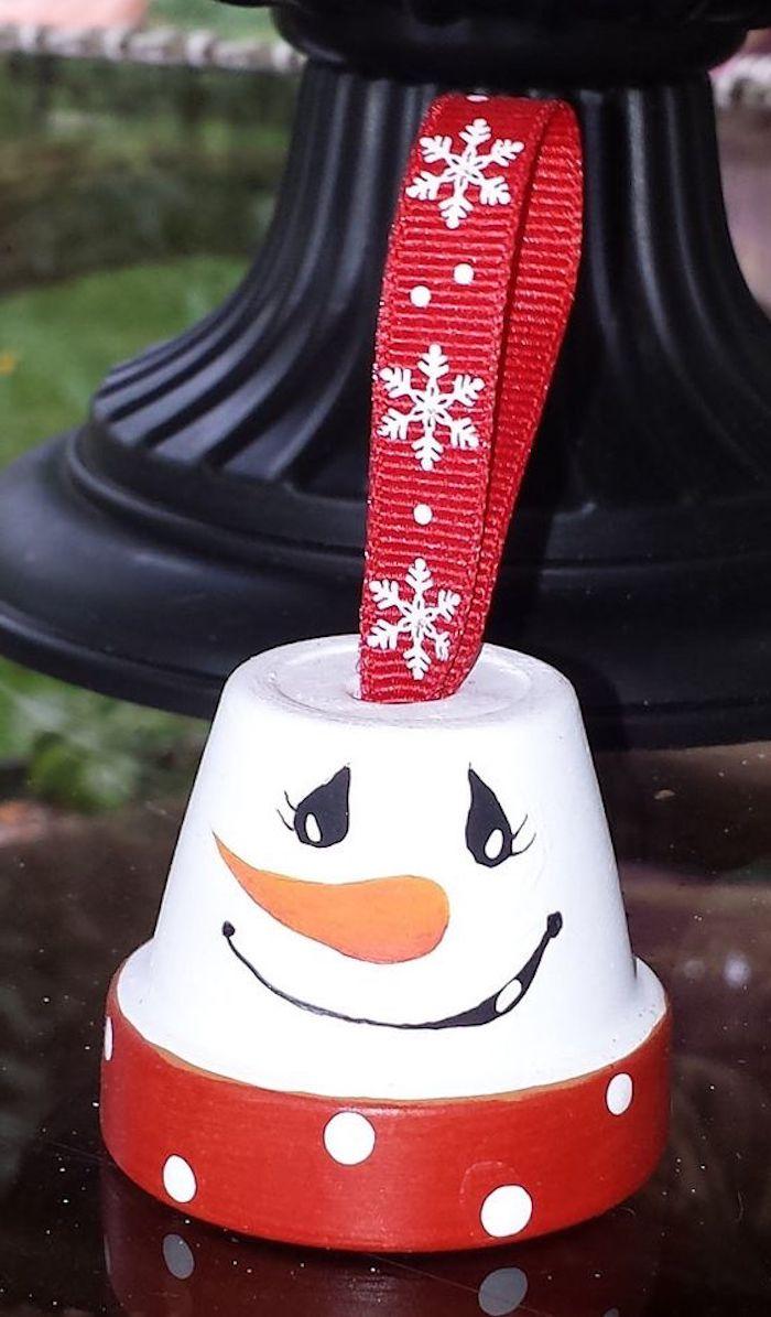 kleiner weißer schneemann mit schwarzen augen und einer orangen nase - schneemann aus blumentopf basteln