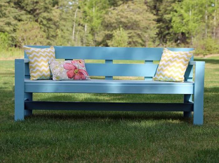 garten mit grass und bäumen - eine blaue kleine diy-gartenbank mit zwei gelben kissen und einem kleinen kissen mit einer rosa blume