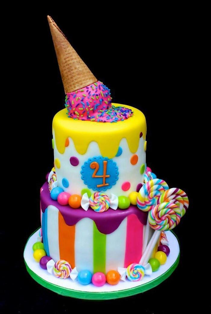 hier ist eine zweistlckige bunte einhorn torte mit einem großen langen horn und mit nummer vier und lila, blauen und gelben kleinen punkten