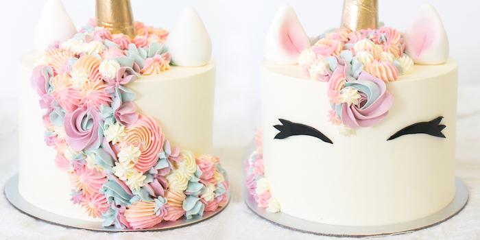 hier ist eine weiße einhorn torte mit schwarzen augen und einer pinken lahne mähne aus sahne - idee für einhorn kuchen