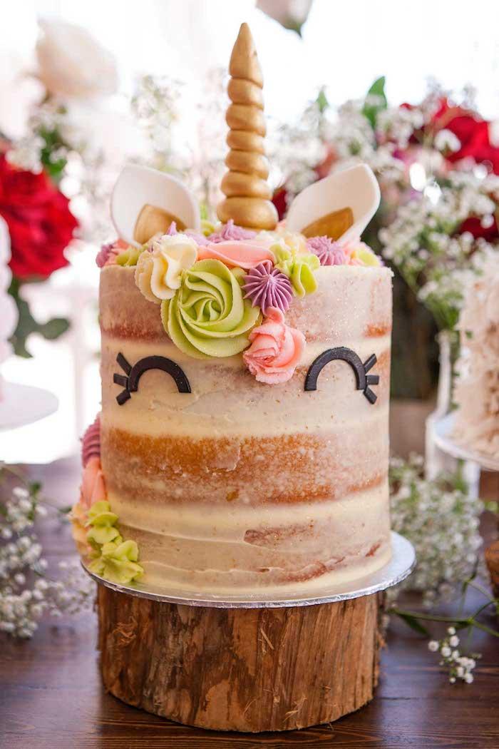 eine große einhorn torte mit schwarzen augen - idee für einhorn kuchen - ein einhorn mit grünen und pinken rosen aus sahne und einem langen goldenen horn