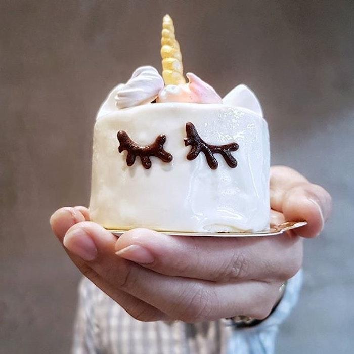 hier ist eine hand und einhorn kuchen - idee für eine kleine weiße einhorn torte mit schwarzen augen und einem kleinen gelben goldenen horn
