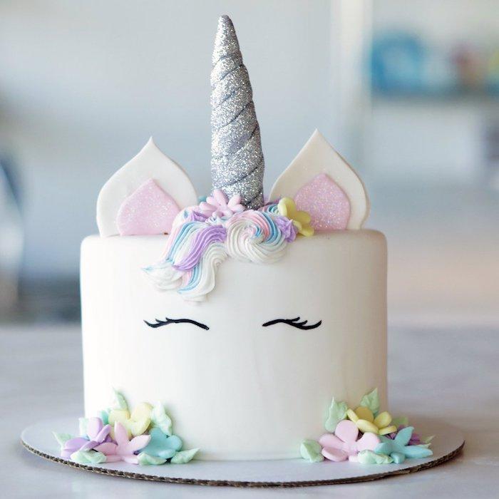 zum thema einhorn kuchen - eine weiße einhorn torte mit einem langen grauen horn und pinken und gelben blumen und einer bunten mähne aus sahne