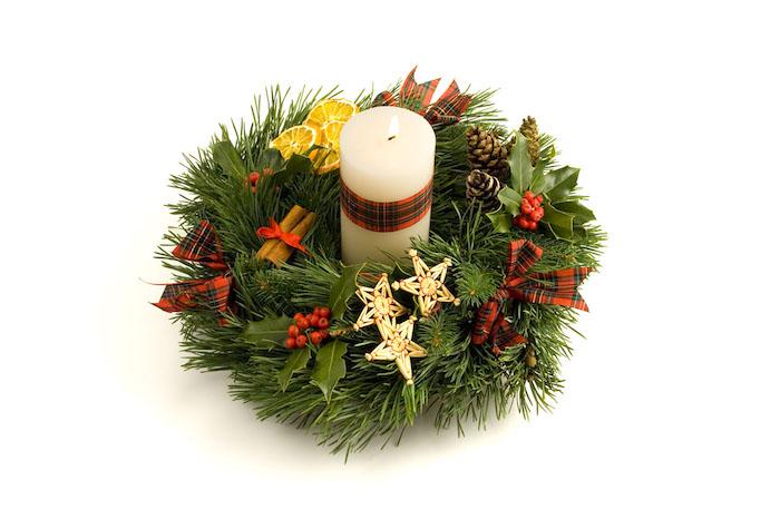 noch ein adventskranz mit drei goldenen sternen und einer großen weißen kerze und ästen mit grünen blättern