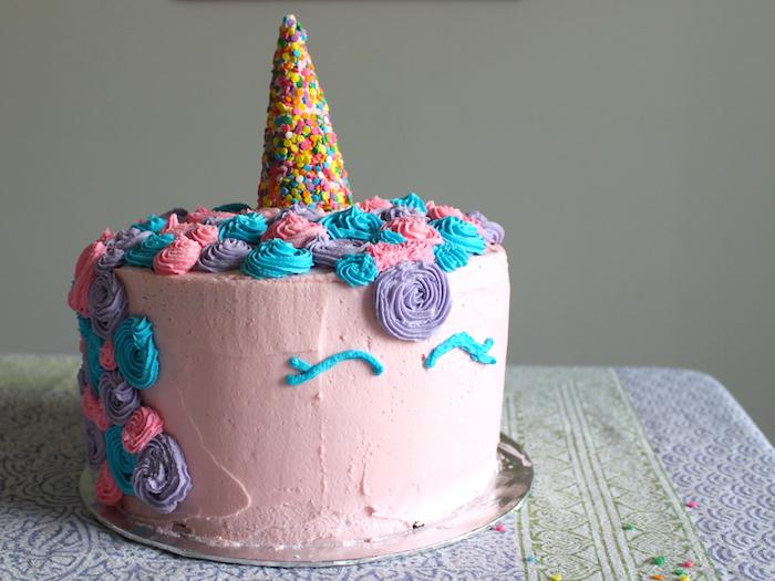 einhorn torte anleitung - hier ist ein pinkes einhorn mit einem großen bunten horn und mit einer mähne aus sahne und mit pinken, blauen und lila rosen