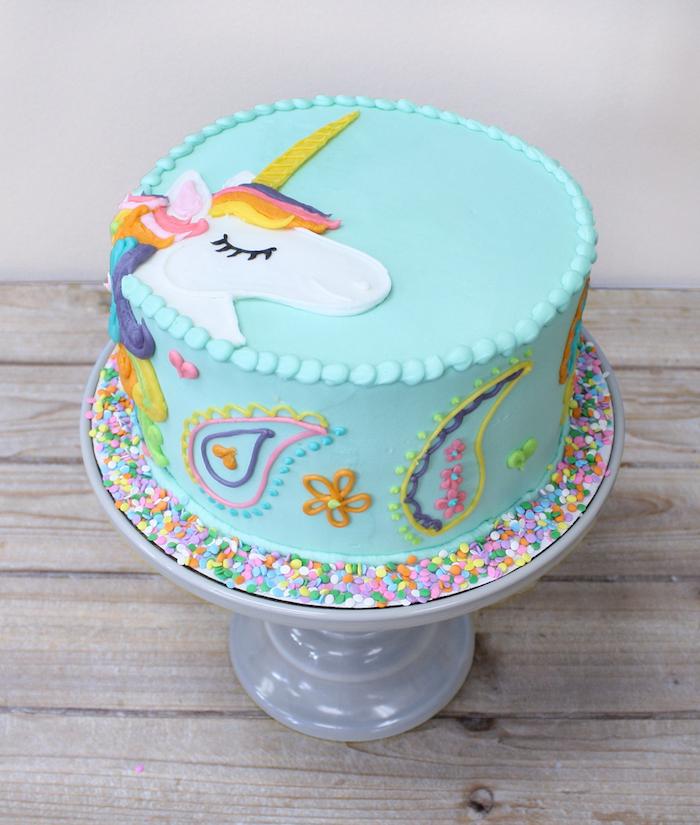 einhorn kuchen rezept - eine blaue einhorn torte mit blumen und einem weißen einhorn mit einer regenbogenfarbenen mähne und einem lanhen horn und schwarzen augen