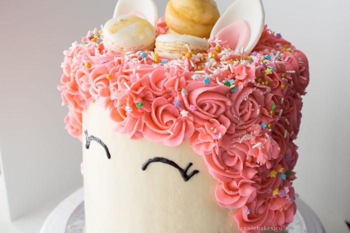 tolle ideen für einhorn kuchen dekof - ier ist eine weiße einhorn torte mit schwarzen augen und mit einer langen pinken mähne aus sahne und einem goldenen einhorn
