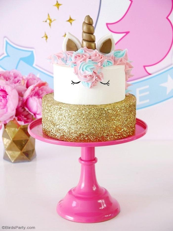 sterne und eine zweistöckige einhorn torte mit einem weißen einhorn mit einer bunten mähne aus sahne und einem kleinen goldenen horn