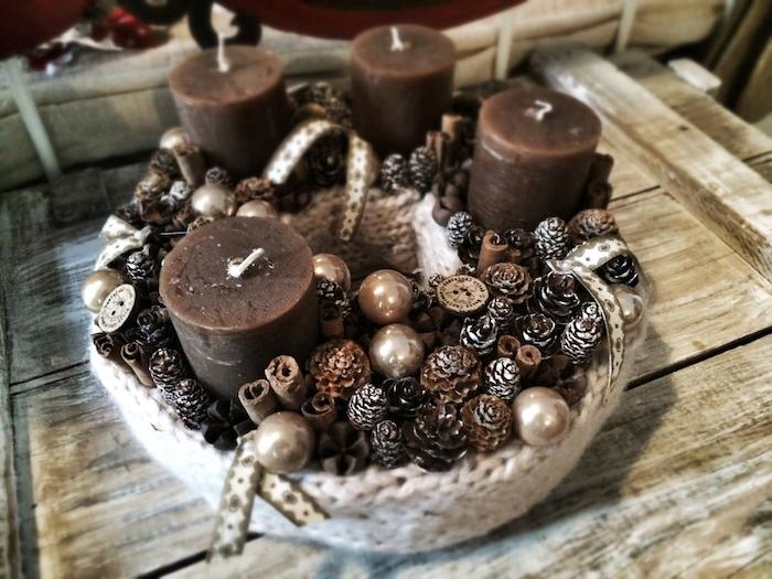 idee zum thema adventskranz selber machen - viele kleine braune zapfen und goldene bälle und vier braune kerzen