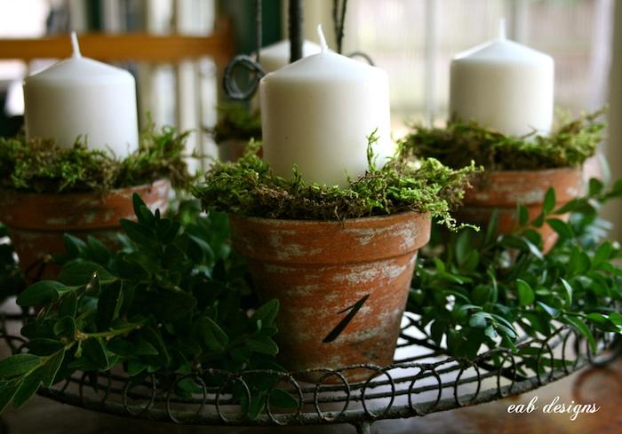 blumentöpfe mit grünen pflanzen und weißen kerzen - einen adventskranz selber machen