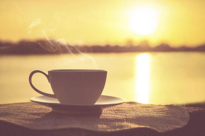 Guten Morgen Bilder - eine Tasse Kaffee mit Dampf im Hintergrund des Sonnenaufgangs
