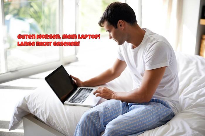 Guten Morgen Bilder - ein junger Mann, der sich aufwacht und mit dem Computer den Tag beginnt