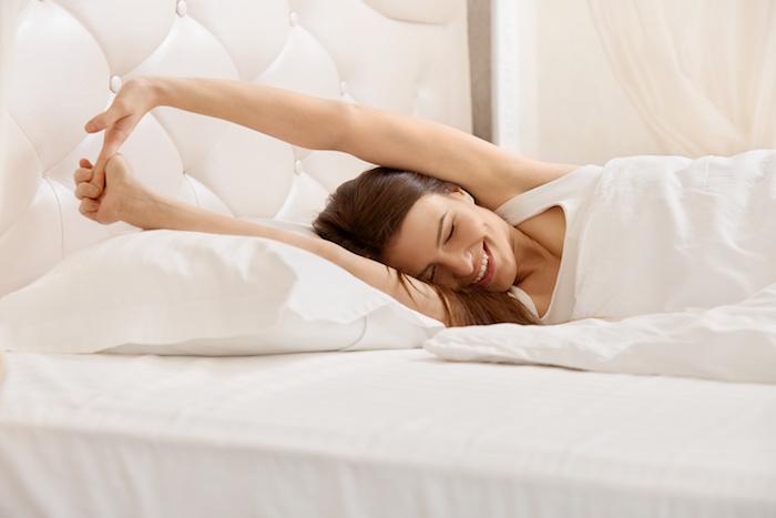 Guten Morgen Bilder - eine Frau liegt im Bett und lächelt sich beim Aufwachen